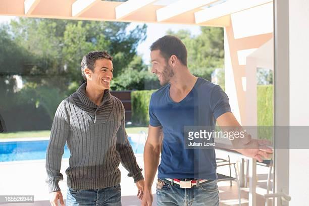 Men opening glass door in backyard