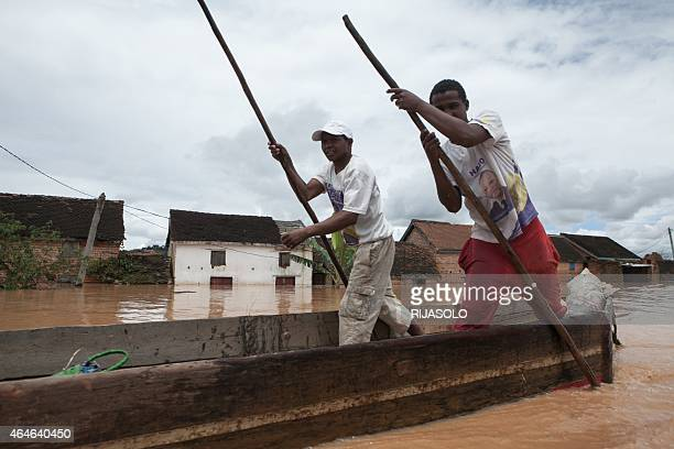 Men operate a pirogue to evacuate residents after the Sisaony river burst and flooded the village of Soavina a suburb of Antananarivo after breaking...