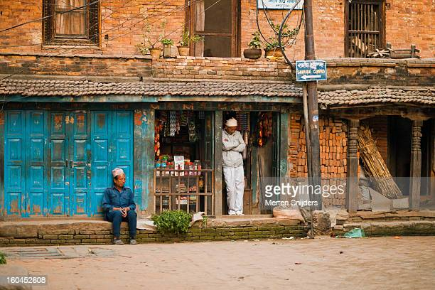 men outside a small grocery store - merten snijders stockfoto's en -beelden