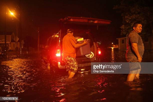 Men pack their belongings after evacuating their house after the Neuse River went over its banks and flooded their street during Hurricane Florence...