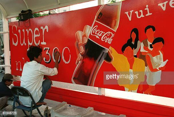 Men paint a CocaCola advertising poster at a bus stop in HoChiMinhCity 11 December In Vietnam the battle in softdrink market continues between two US...