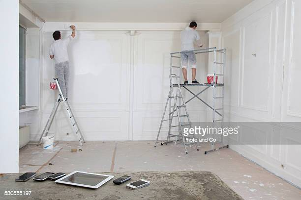 men painting a wall with tablet and phone