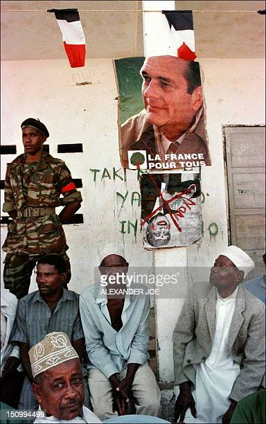 Men participating in secessionist rally sit under a poster of French President Jacques Chirac 17 August in Domoni the second biggest town on the...