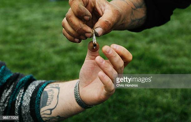 Men pass a marijuana cigarette to each other during a promarijuana rally at Civic Center Park with the Colorado State Capitol Building in the...