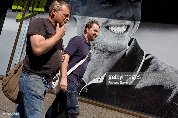 Men pass a Nike retail poster of Northern Irish golfer Rory McIlroy in central London The two males walk past in good humour one inhaling from his...
