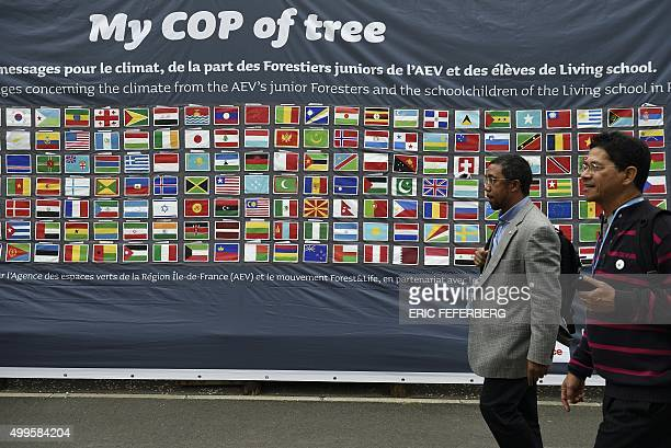 Men pass by a bannner depicting the flags of all the countries and asking for planting trees during the COP21 United Nations Conference on climate...