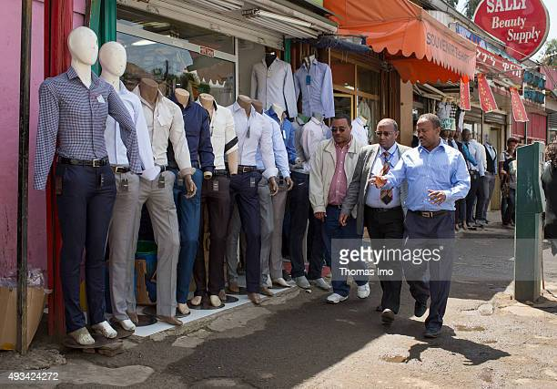 Men pass by a shop for mens clothes on October 12 2015 in Addis Abeba Ethiopia