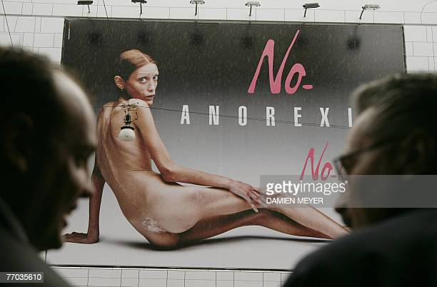 Men pass by an italian advertising campaign featuring the photo of an emaciated girl 26 September 2007 in Milan in the middle of Milan fashion week...