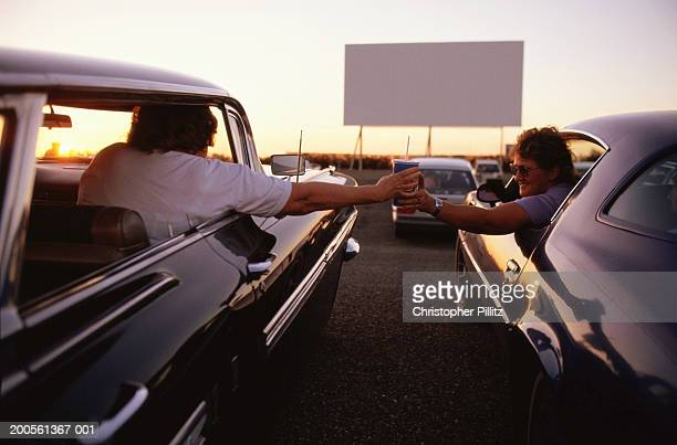 Men passing cup between cars in drive-in cinema, rear view