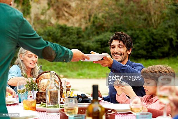 Men passing dish at outdoor meal table in yard