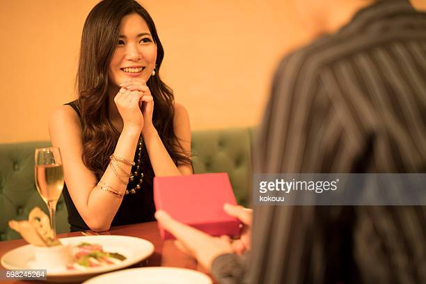 レストランで恋人に贈り物を渡す男性 - 誕生日の贈り物 ストックフォトと画像