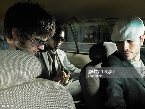 men paying a taxi driver