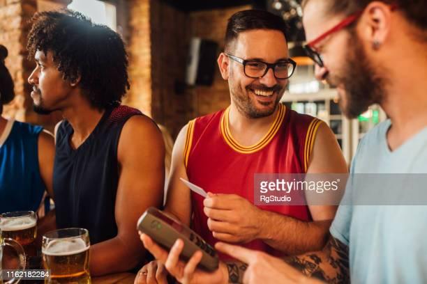mannen betalen met creditcard en glimlachend - sports round stockfoto's en -beelden