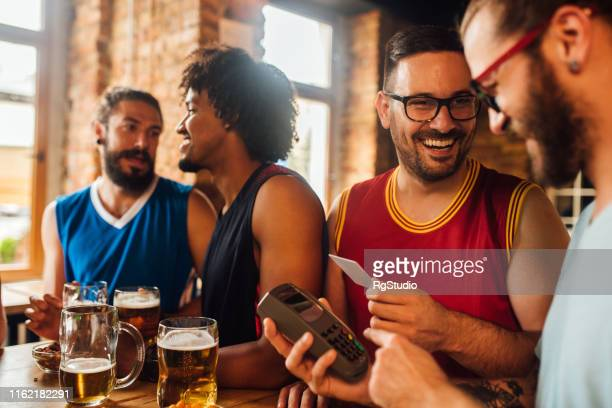 men paying with credit card and smiling - charging sports stock pictures, royalty-free photos & images
