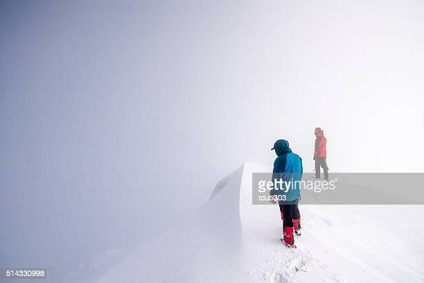 2 men peering over a mountain peak into the clouds