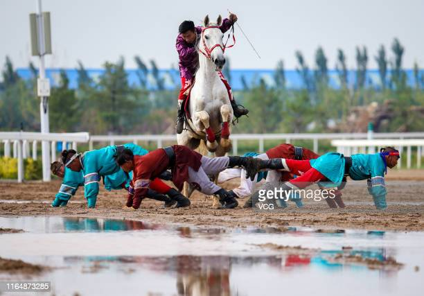 Men perform horse riding skills during the 6th Inner Mongolia International Equestrian Festival on July 27, 2019 in Hohhot, Inner Mongolia Autonomous...