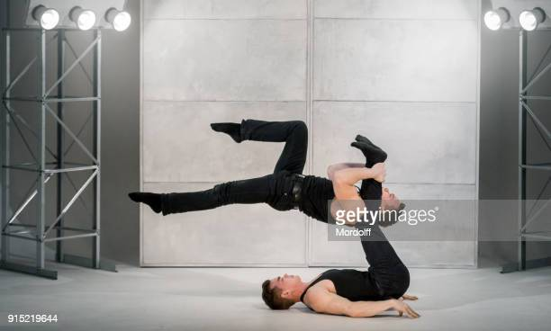 men performs gymnastic power exercises - black shirt stock pictures, royalty-free photos & images