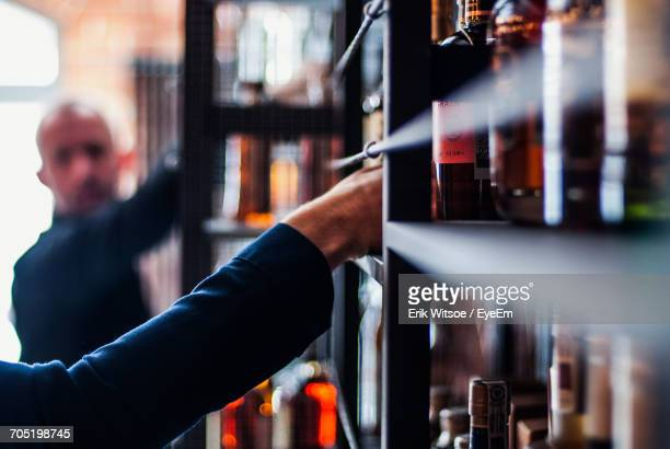 Men Picking Alcohol From Shelf In Store