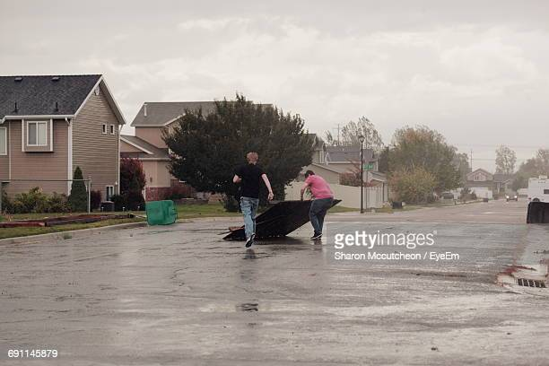 men picking damaged fence on wet street against cloudy sky during tornado - storm season tornadoes stock photos and pictures
