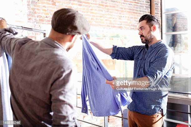 Men picking out clothes on rack