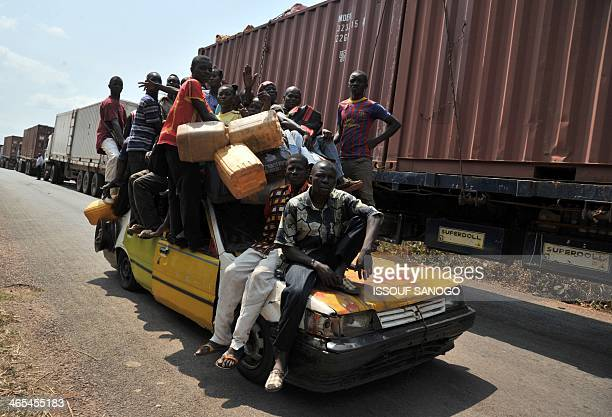 Men piled onto a collective taxi pass by a supply convoy from Cameroon being escorted by French soldiers of the Sangaris operation and Rwandan...