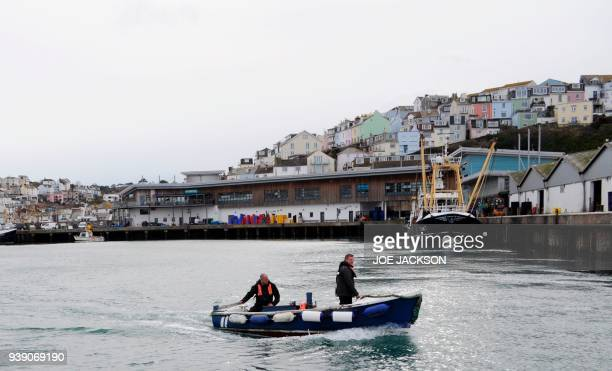 Men pilot a dingy in the harbour in the fishing town of Brixham on the south coast of England on March 26 2018 On the dockside in Brixham a bustling...