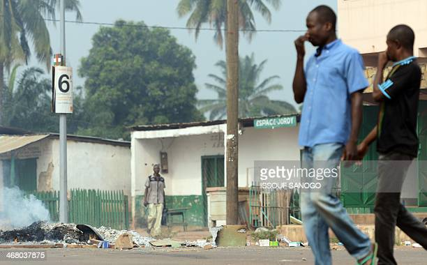 Men pinch their noses as they walk past a charred body on February 9 2014 in central Bangui where according to witnesses at least ten people have...