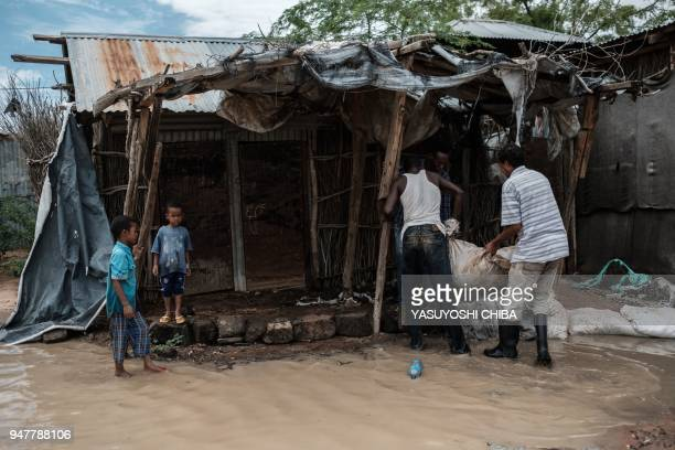 Men place a sandbag in a shelter as they attempt to halt the rise of floodwaters after a heavy rainy season downpour at the Dadaab refugee complex,...