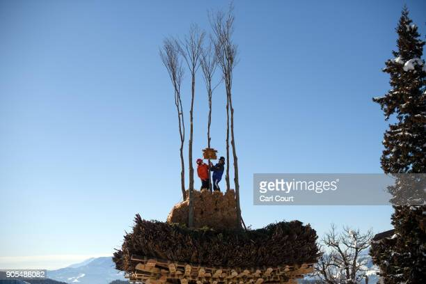 Men place a Shinto prayer box atop the shrine as they finish its construction during preparations for the Nozawaonsen Dosojin Fire Festival on...