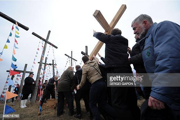 Men place a wooden cross on a hill while celebrating Palm Sunday in the town of Oshmiany some 130 kilometers northwest of Minsk on March 29 2015 AFP...
