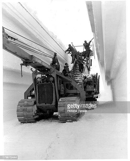 Men place arch supports in the tunnel to main trench of the permanent camp at Century Camp Greenland