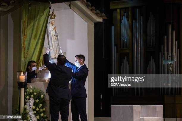 Men place the Image of Our Lady of Fatima at the Chapel of Apparitions after the procession Prayers of the rosary at the Chapel of the Apparitions in...