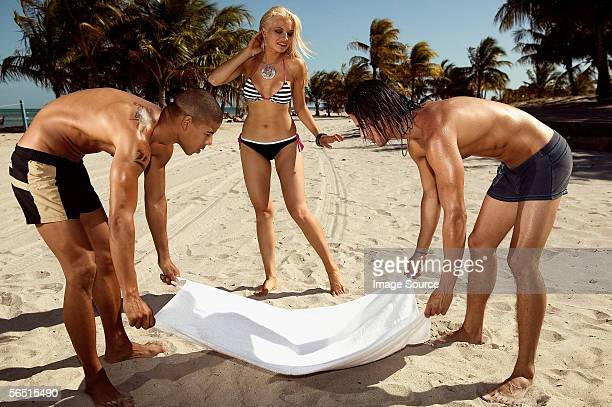 Men placing towel on beach for woman