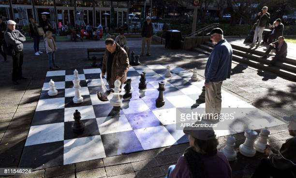 Men play a game of chess on a giant chess board painted on tiles in Sydney's Hyde Park on July 10 2017 / AFP PHOTO / William WEST
