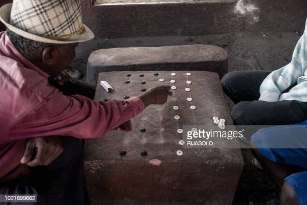 Men play a game of Fanorona in the capital Antananarivo on June 20, 2018. - Fanorona is a traditional Malagasy game played since the royal era. It is...