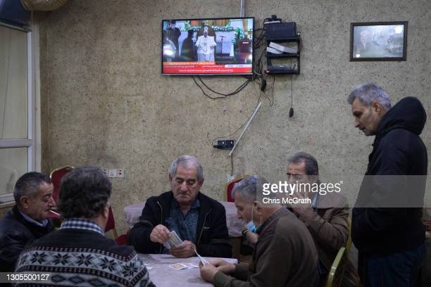 Men play cards at a tea house in front of a television screen showing live footage of Pope Francis on March 05, 2021 in Erbil, Iraq. Pope Francis...