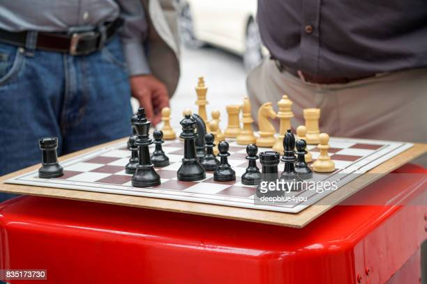Men play chess on a red rubbish bin