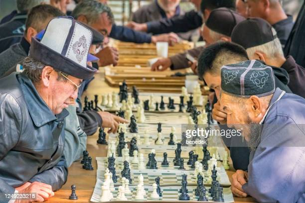 men play chess outdoors in osh kyrgyzstan - kyrgyzstan stock pictures, royalty-free photos & images
