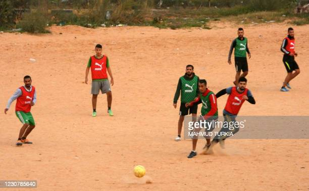 Men play football at a dirt pitch in Libya's capital Tripoli on January 25, 2021.