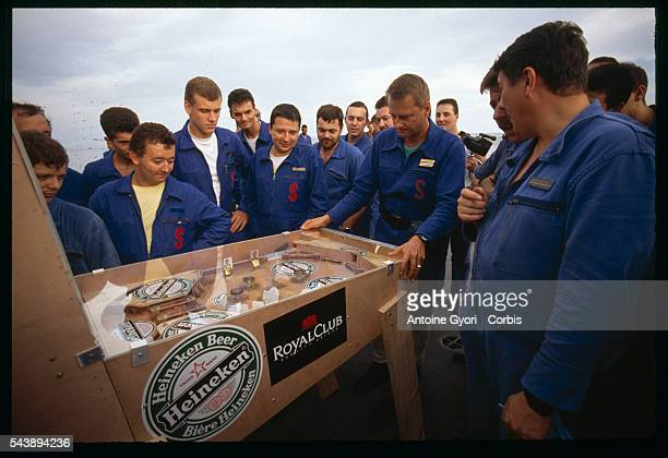 Men play pinball aboard the French warship Le Marne in the Persian Gulf