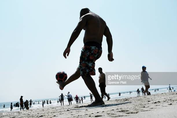 Men play soccer along Rockaway Beach as visitors try to stay cool on a hot summer day on August 22, 2017 in the Queens borough of New York City. New...