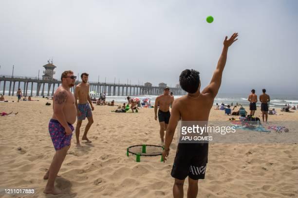 Men play spike ball on the beach amid the novel coronavirus pandemic in Huntington Beach, California on April 25, 2020. - Orange County is the only...