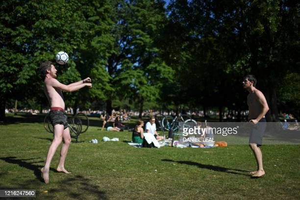 TOPSHOT Men play with a football as people enjoy the sunshine at Victoria Park in east London on May 30 ahead of the coming into force of the first...