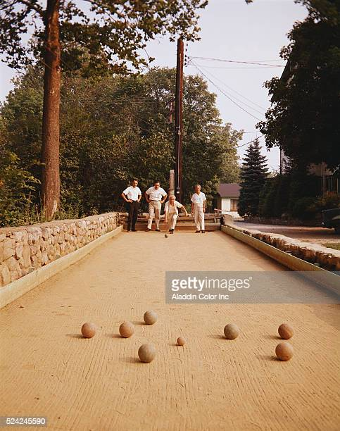 Men playing a game of bocci ball on the grounds of Louis Lake House | Location Swartswood New Jersey USA