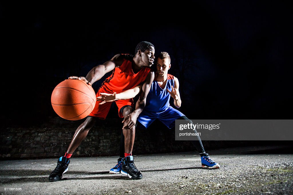 Men playing basketball at night : Stock Photo