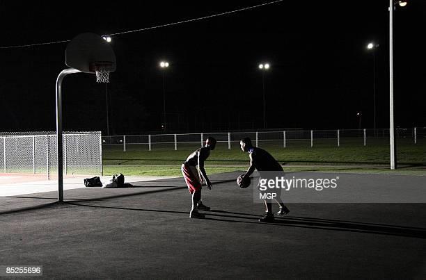 men playing basketball at night