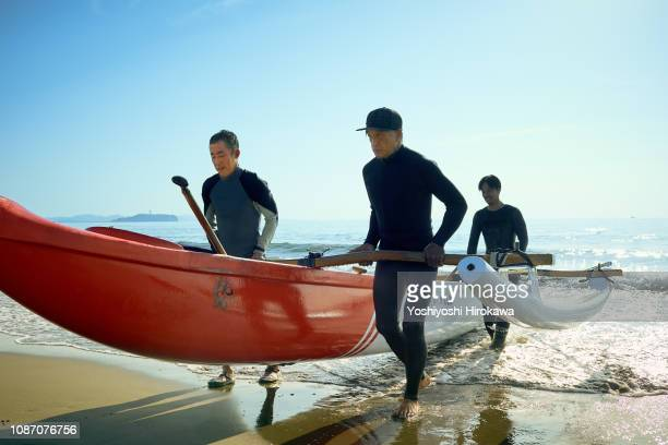 Men playing canoe at Pacific Ocean.