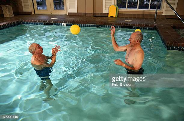 Men Playing Catch in a Swimming Pool