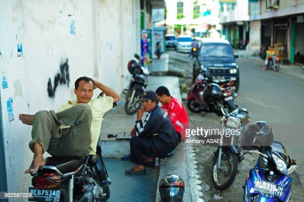 2 men playing chess while the other is resting on motocycle Banda Aceh Sumatra Indonesia
