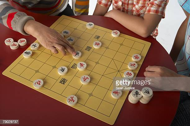 Men playing Chinese chess, close-up on hands
